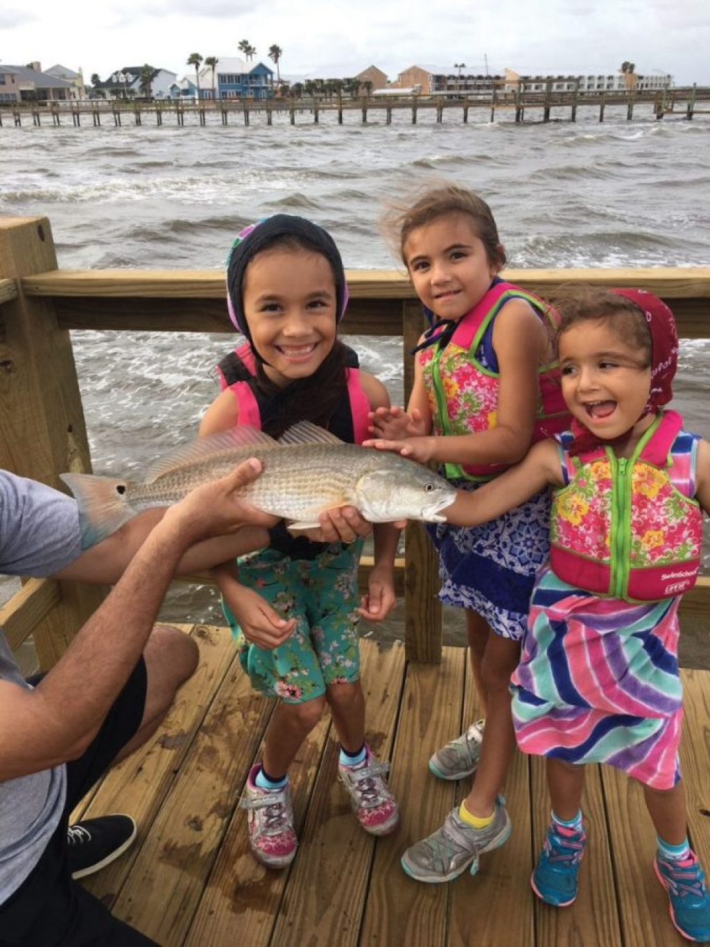 Nine-year-old Isabella Rivera with the biggest fish of her life, 22-inch redfish caught in Aransas Bay on a fishing pier using live shrimp. The fish was released. Joining her were her sisters Abryanna (seven) and Katalyna (four). Dad Mark held the fish.