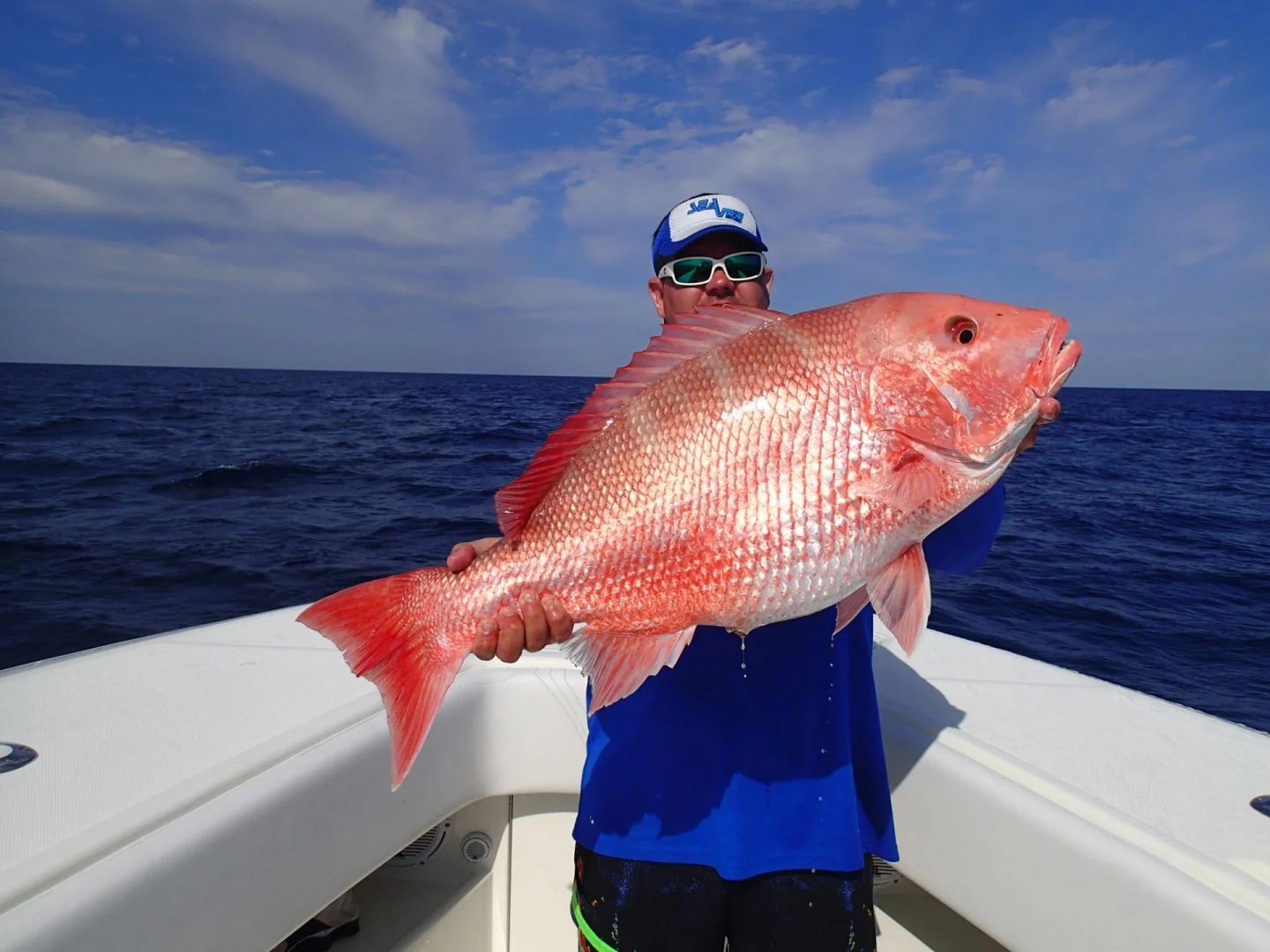A man on a boat holding a big Red Snapper in Boca Grande, Florida