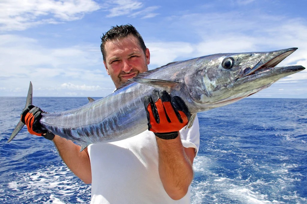 A man holds a large Wahoo with the open water behind him