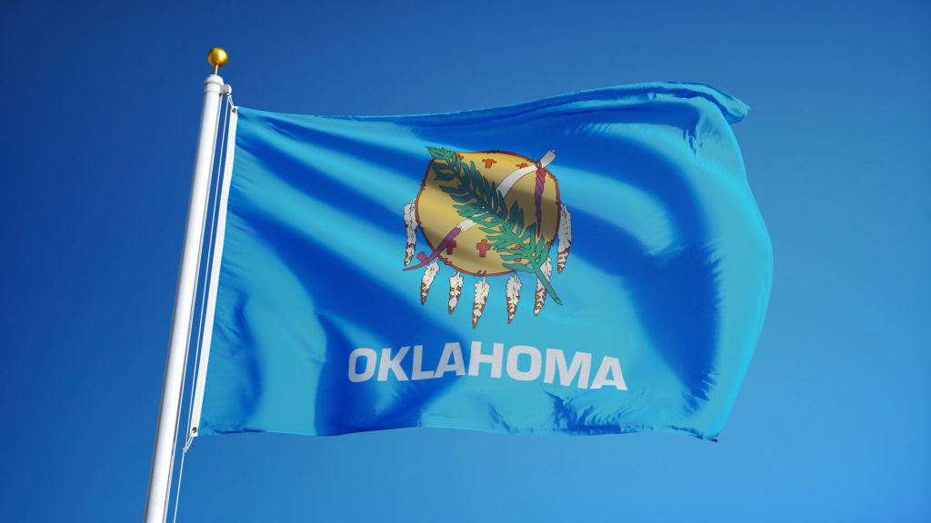 The state flag of Oklahoma flying in the wind in front of a blue sky.
