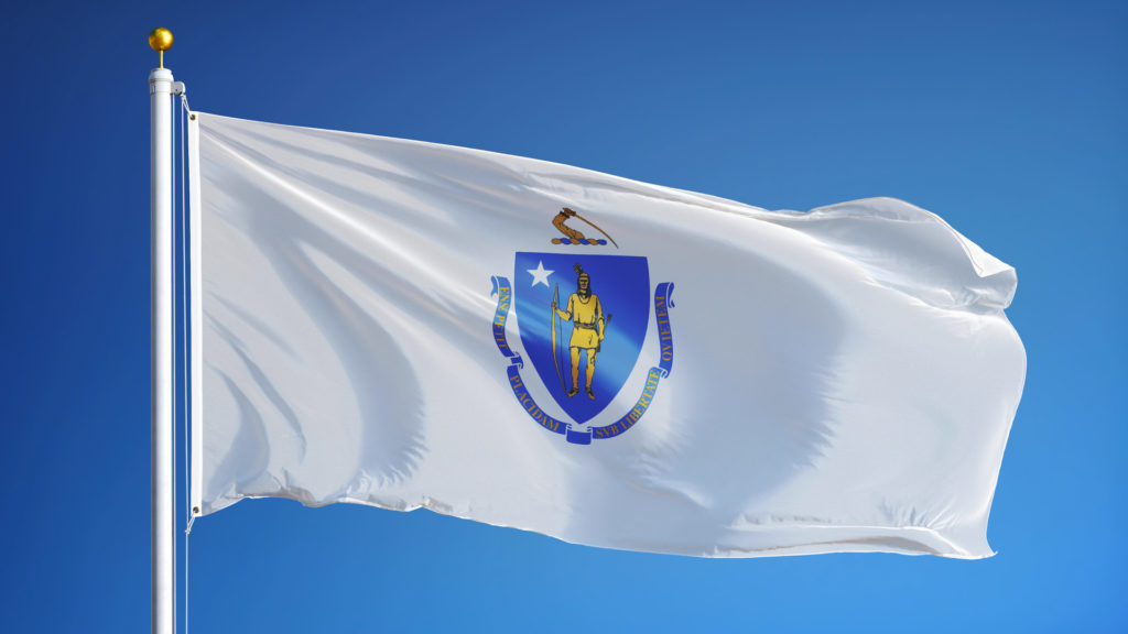 The Massachusetts flag on a flagpole with the blue sky in the background