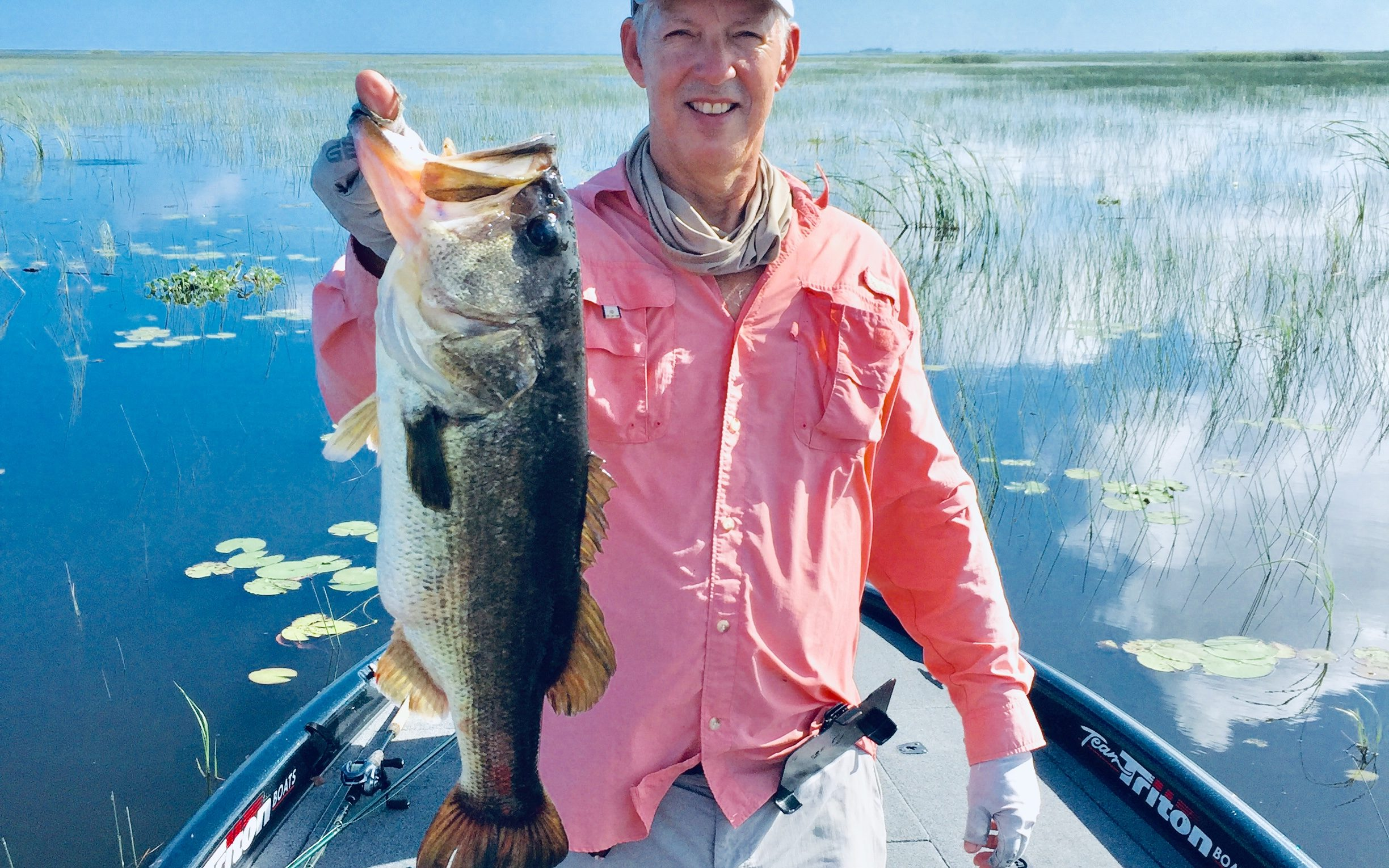 Smiling angler holding big Largemouth Bass on a boat in Florida