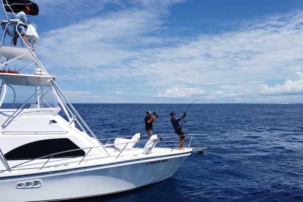 Two fishermen standing on the bow of a charter boat, one reeling in fish, the other taking a video of it