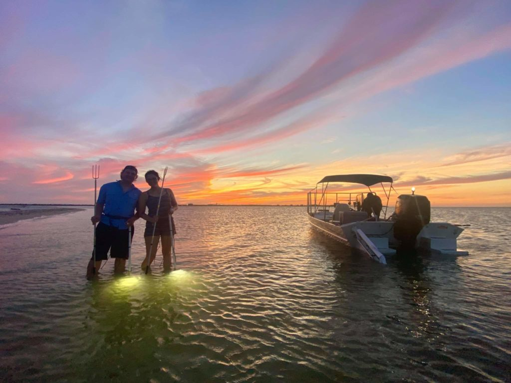 Two anglers standing in the water by their boat with Flounder gigs in their hands