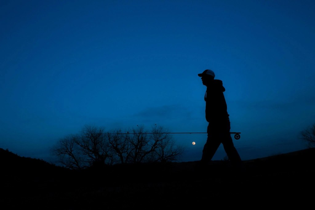 An angler walking at night with a fly fishing rod in his hand.