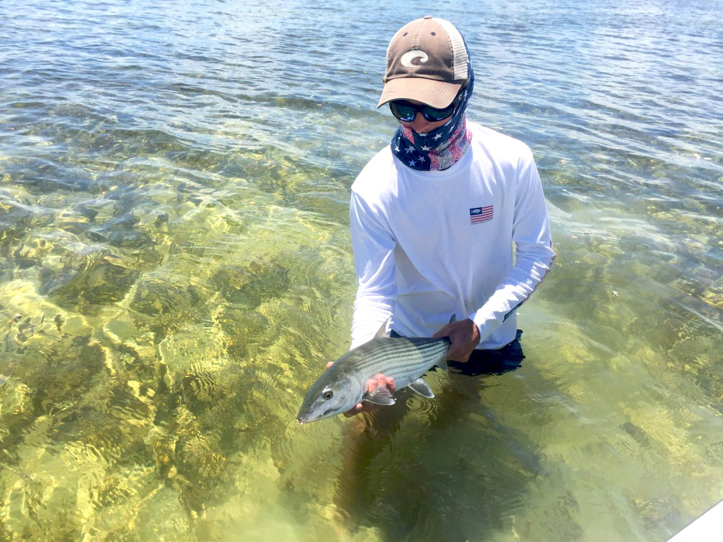 A young man holding a Bonefish in the waters of the Florida Keys