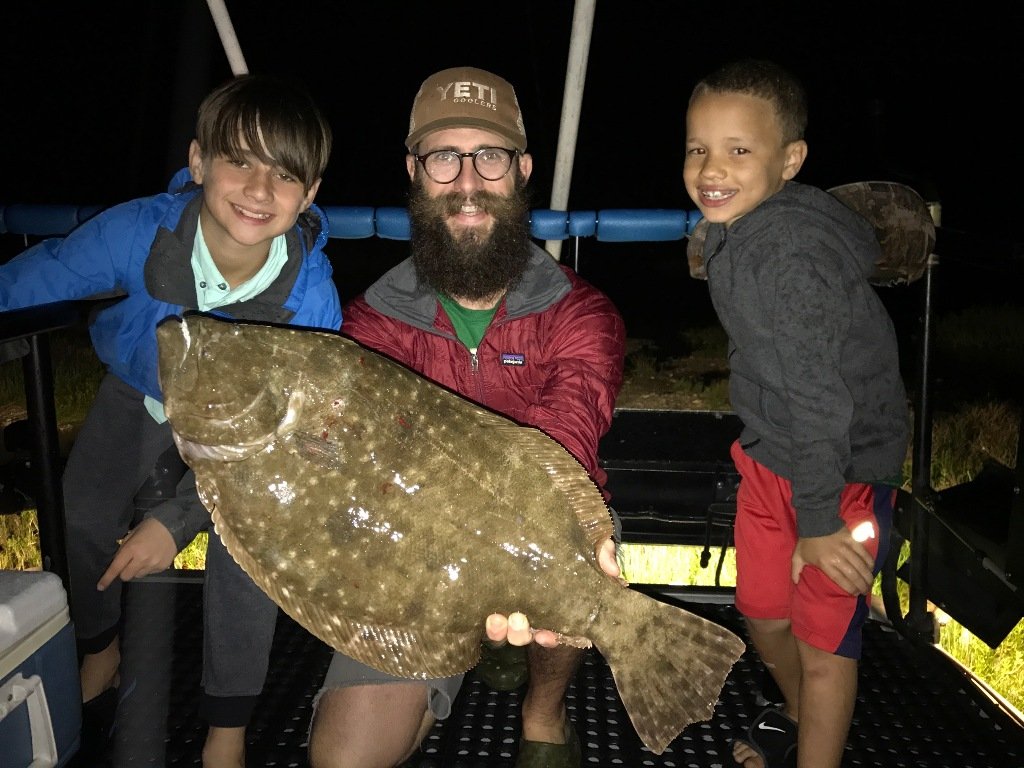 Man and two children holding a huge Flounder