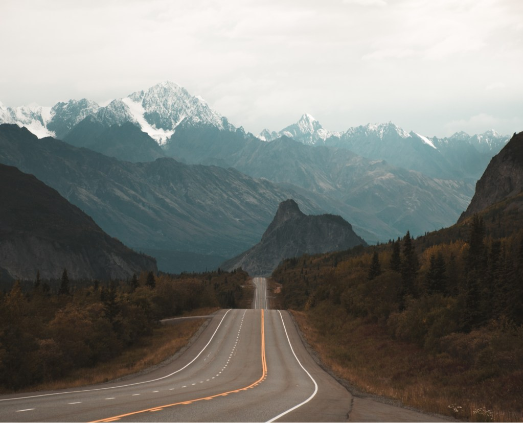 a view of the Alaskan Highway with snow caped mountains in the background