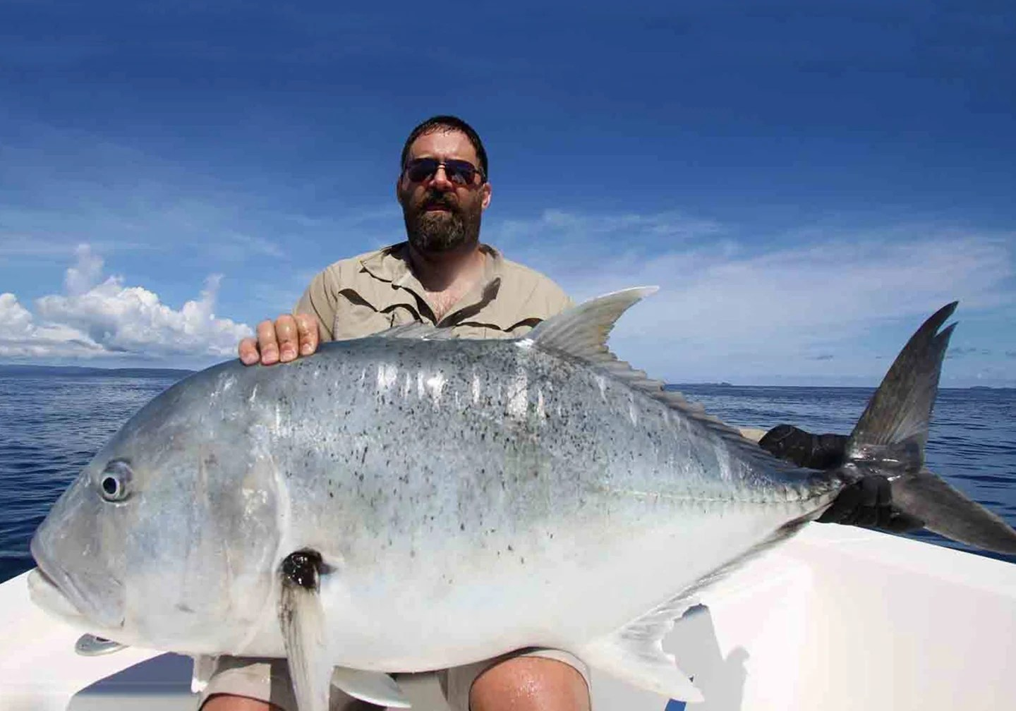 A male angler with a large Giant Trevally fish on his lap
