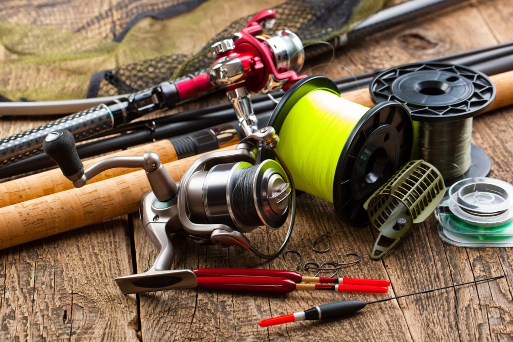 A collection of brightly colored lures, tackle, and fishing gear arranged on a wooden table