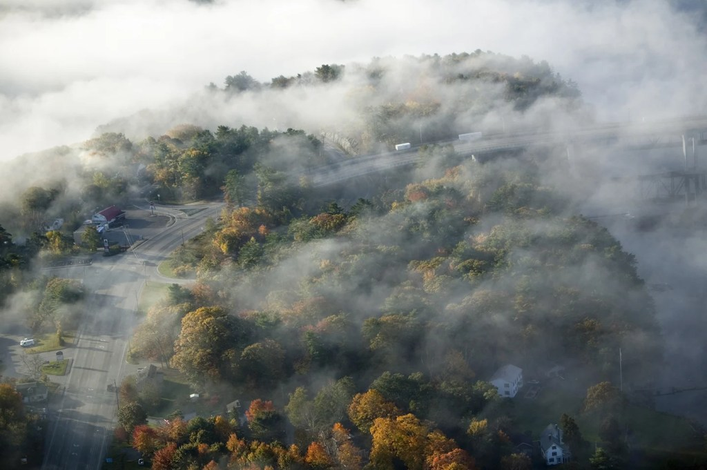 An aerial shot of fog over the town of Bath, Maine