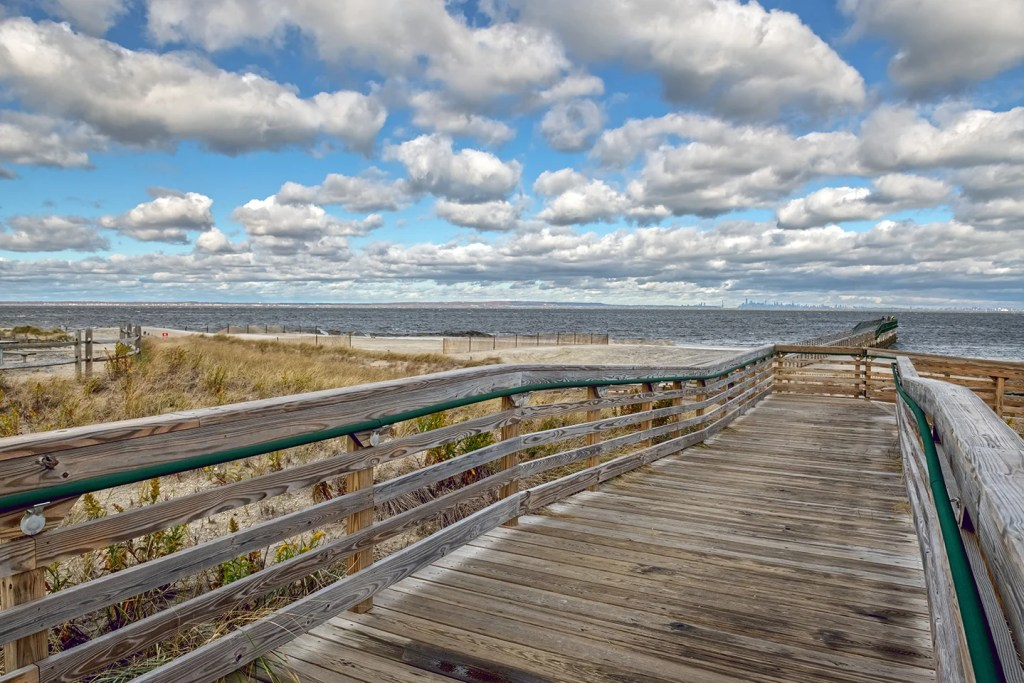 A boardwalk leading down to a fishing pier in Bayshore Waterfront Park, NJ. The New York skyline is visible on the horizon.