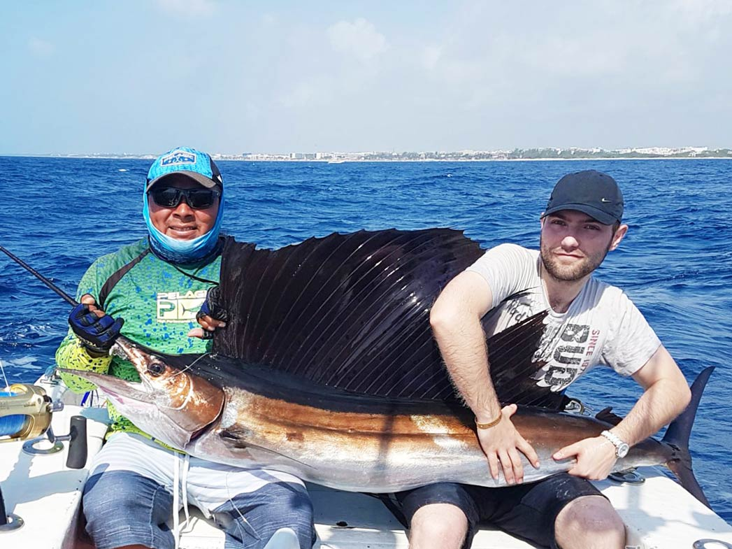 Two men hold a huge Sailfish as they sit on a sportfishing vessel with the Caribbean Sea behind them