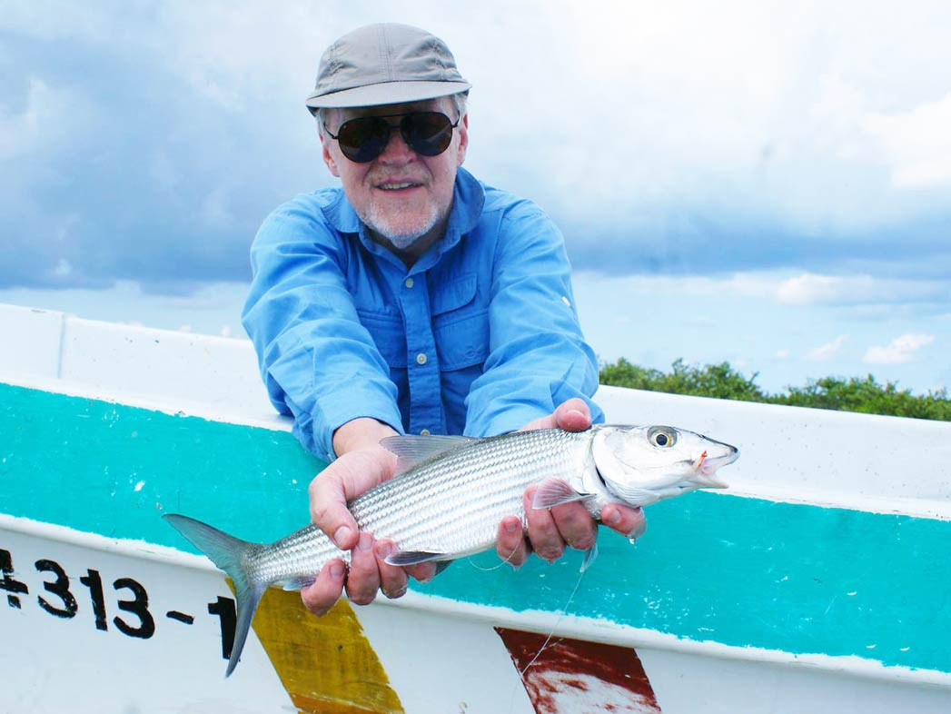 A man leans over a boat holding a Bonefish and smiling