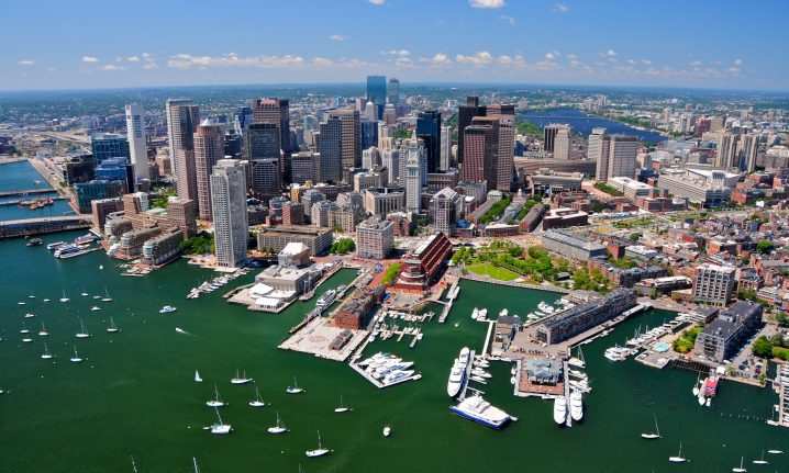 An aerial view of Boston, MA with boats in the water in the foreground