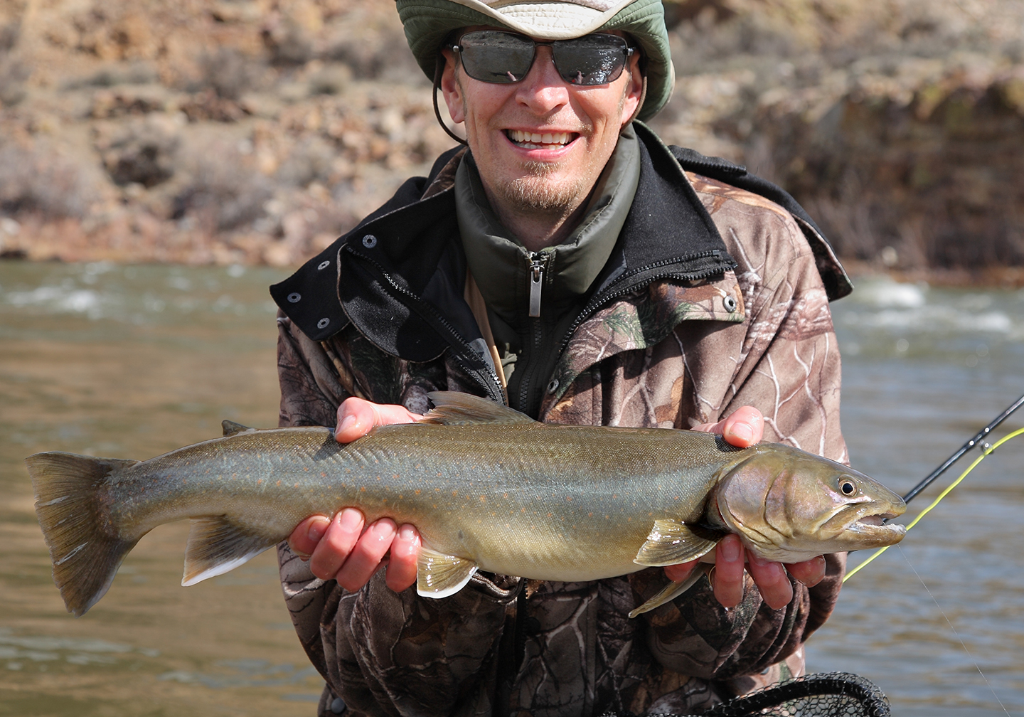 A happy angler holding a Bull Trout, one of the rarest Trout of North America