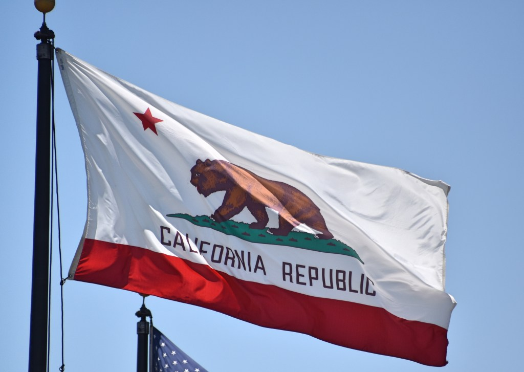 The California state flag flying with blue sky in the background