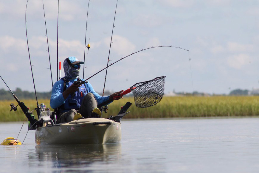 A kayak fisher holding a fishing rod and a catch net in calm sea marshes