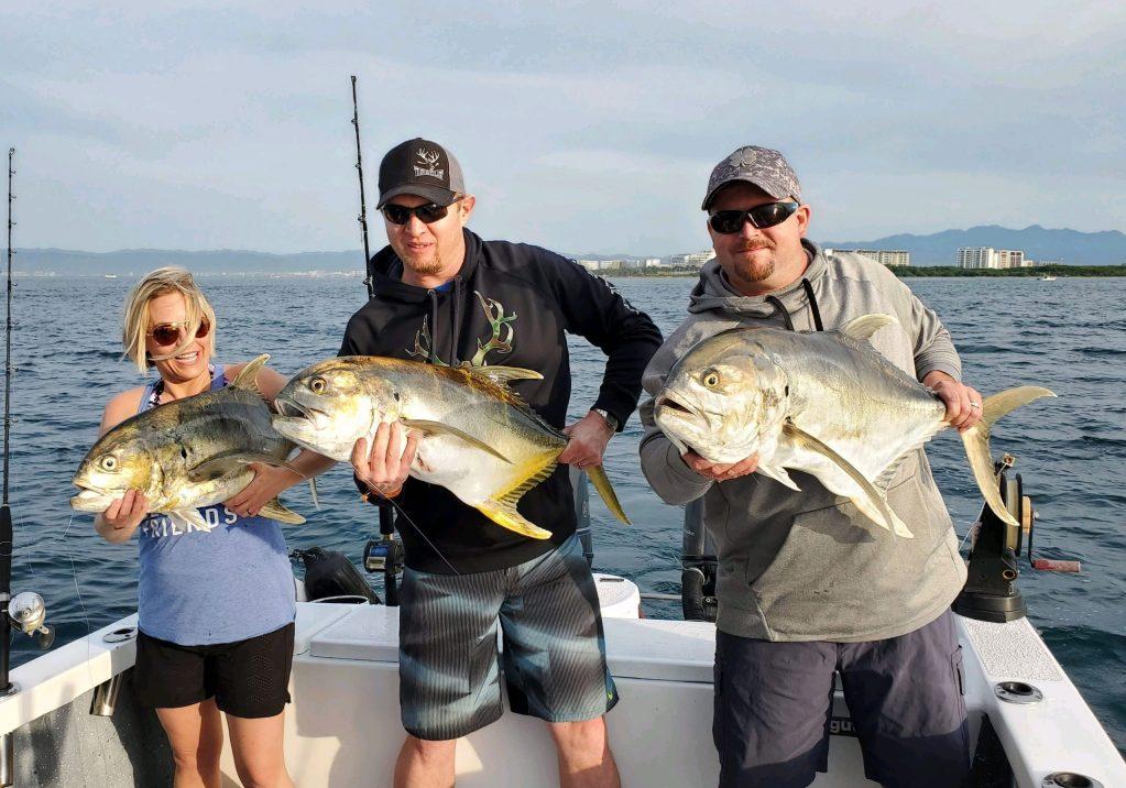 three happy people holding jack crevalle fish