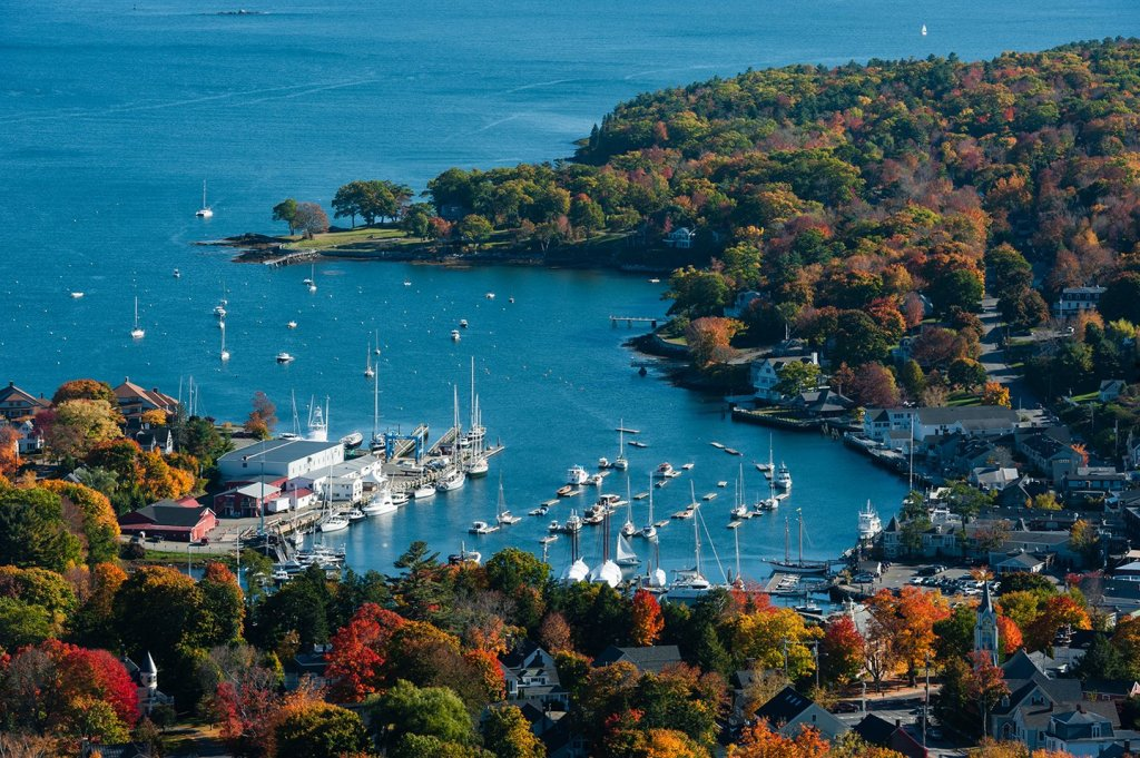 An aerial view of Camden, Maine, with boats in the water and autumn trees to the bottom and right