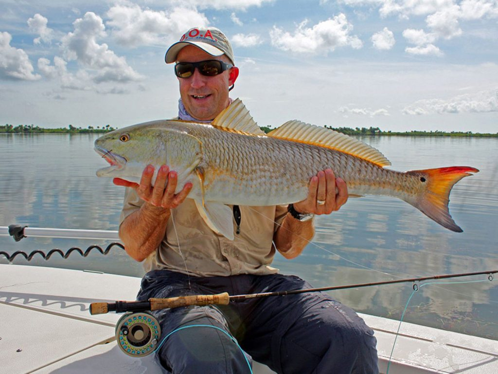 A fly angler with his rod in his lap holding a big Redfish while sitting on a boat