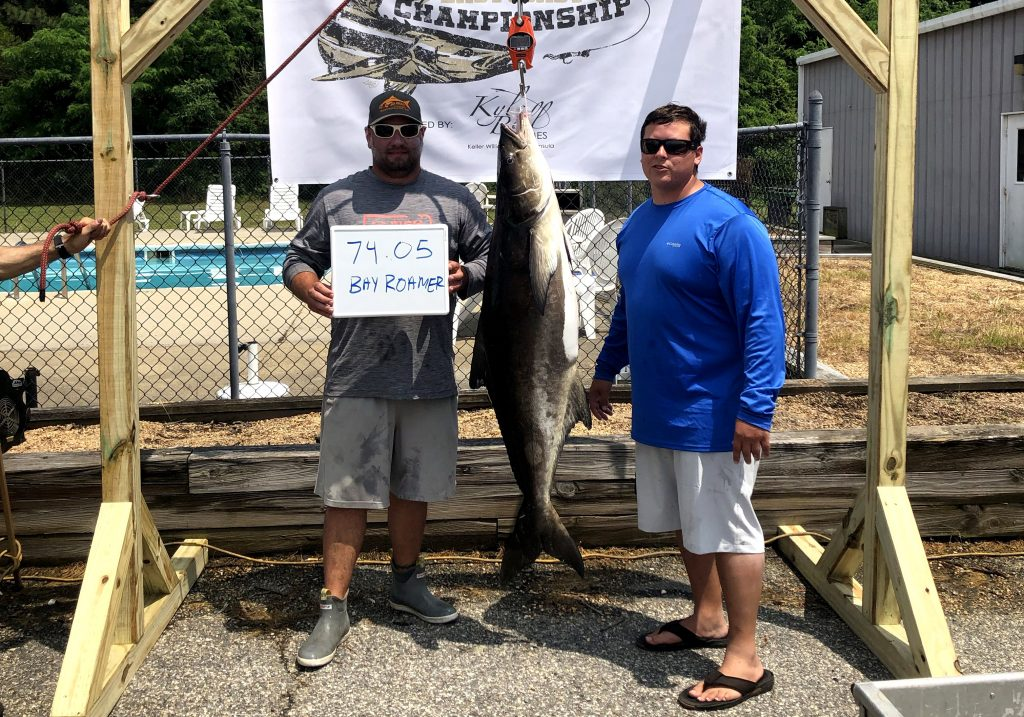 Two anglers posing with their tournament-winning cobia hanging between them