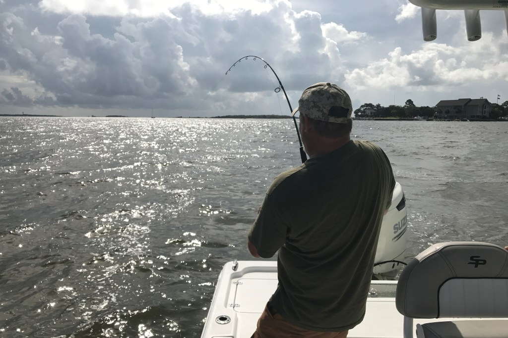An angler fighting a fish on a boat near Folly Beach, SC