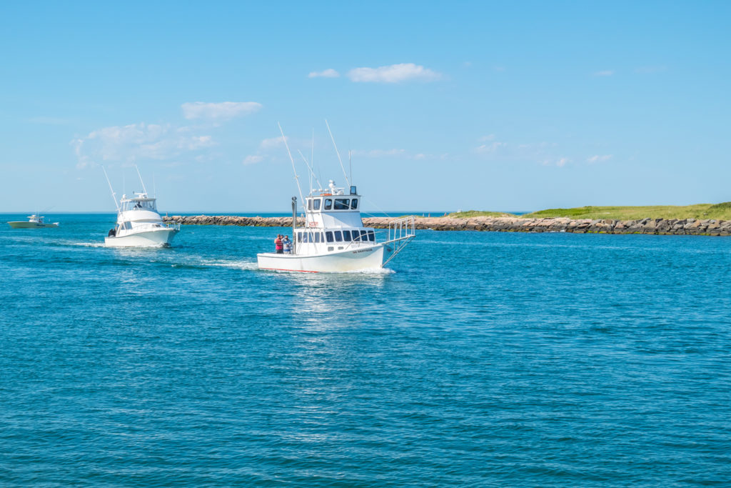 Two charter boats out on the water on a sunny day near Montauk