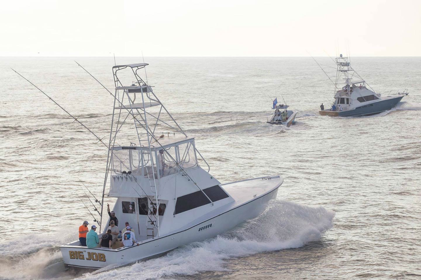 Two large and one small charter fishing boats head out on the choppy waters of the Gulf of Mexico