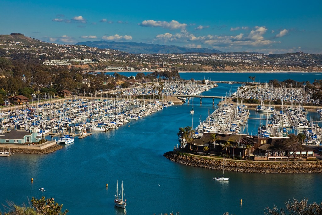 An aerial view of Dana Point harbor, with lots of white charter boats in the marina in the center and coastline stretching into the distance
