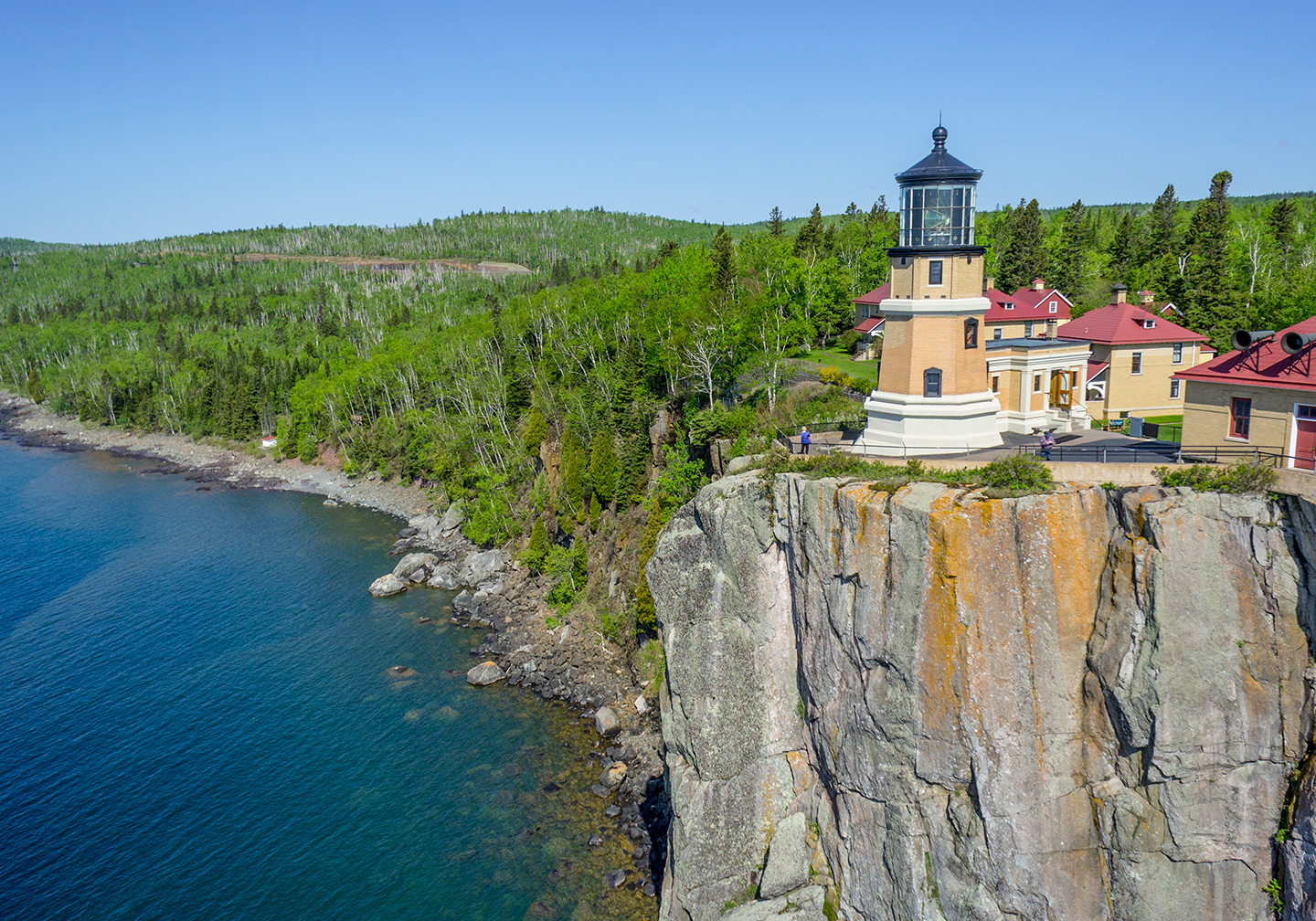 A lighthouse on a tall, gray cliff in Duluth, MN, with green forest behind it and the blue waters of Lake Superior beneath it.