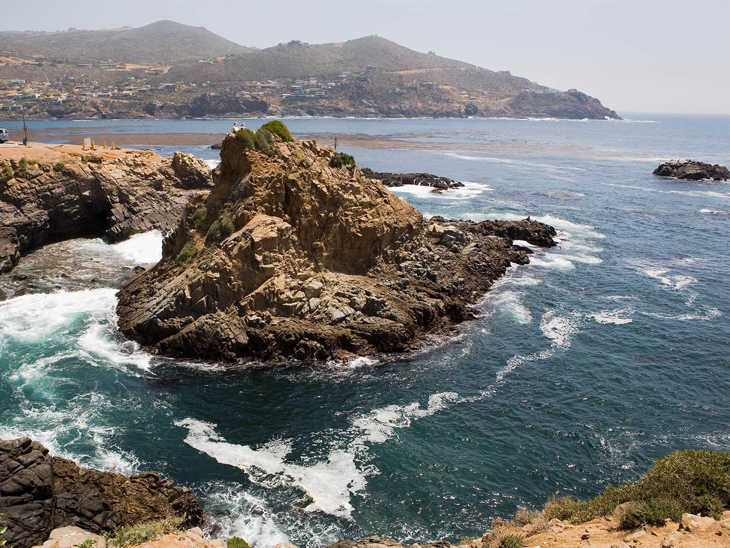 Rocks stick out of the water in the All Saints Bay looking towards Ensenada