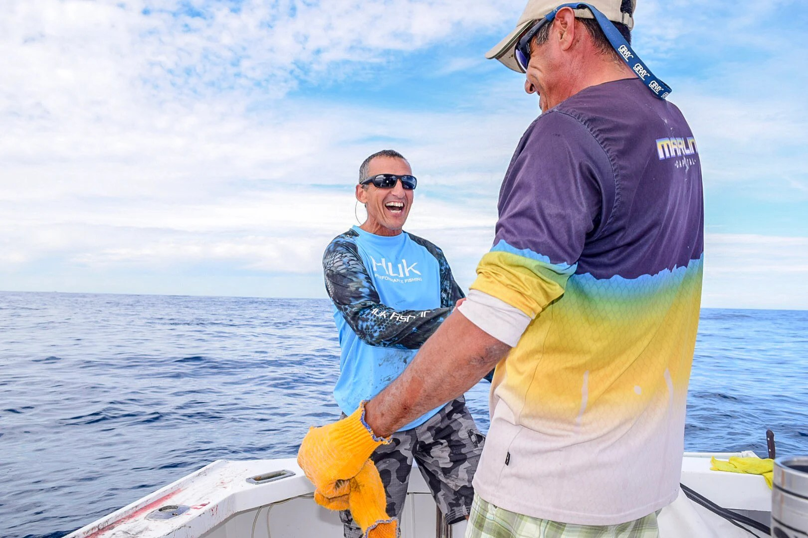 two excited anglers shaking hands after catching a fish