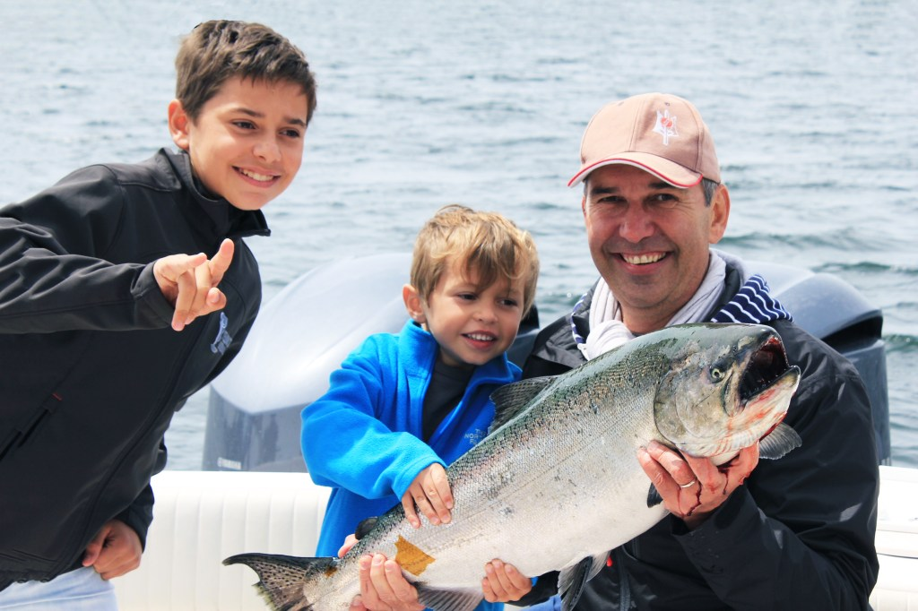 Family fishing Ucluelet: a father angler with his two sons, holding a salmon on a fishing boat near Ucluelet, British Columbia, Canada