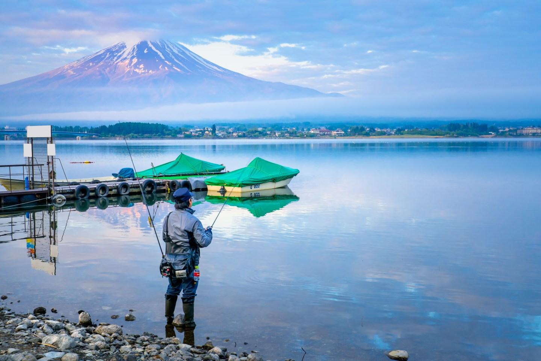 Fisherman Stand in Lake Kawaguchi Fishing in the Morning with Background of Mount Fuji.