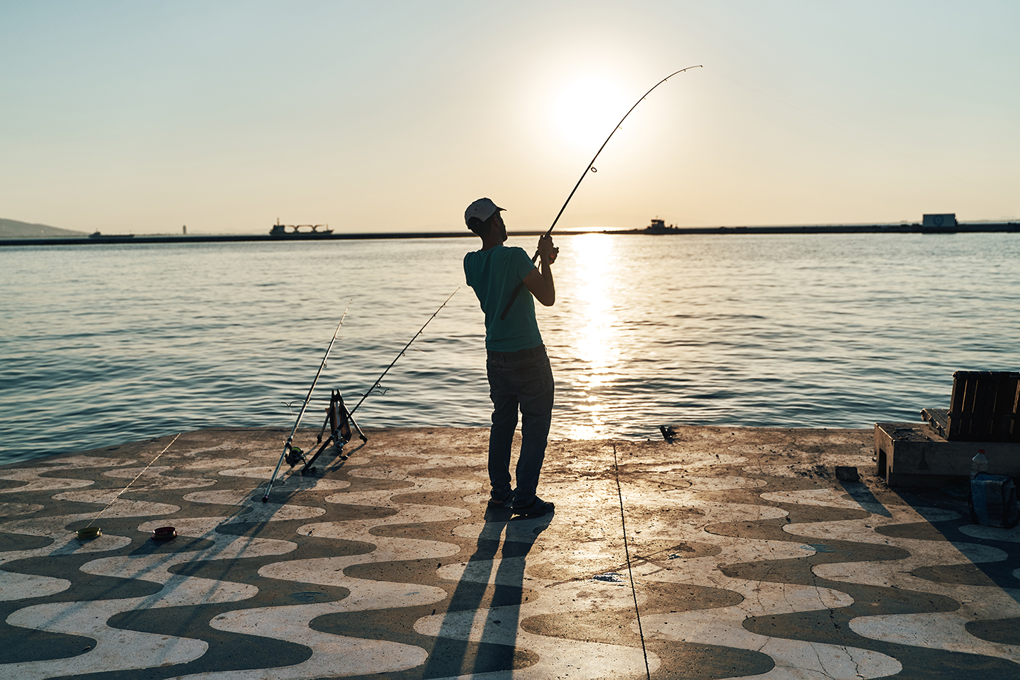 An angler facing the sun and reeling in a fish on a tiled fishing pier.