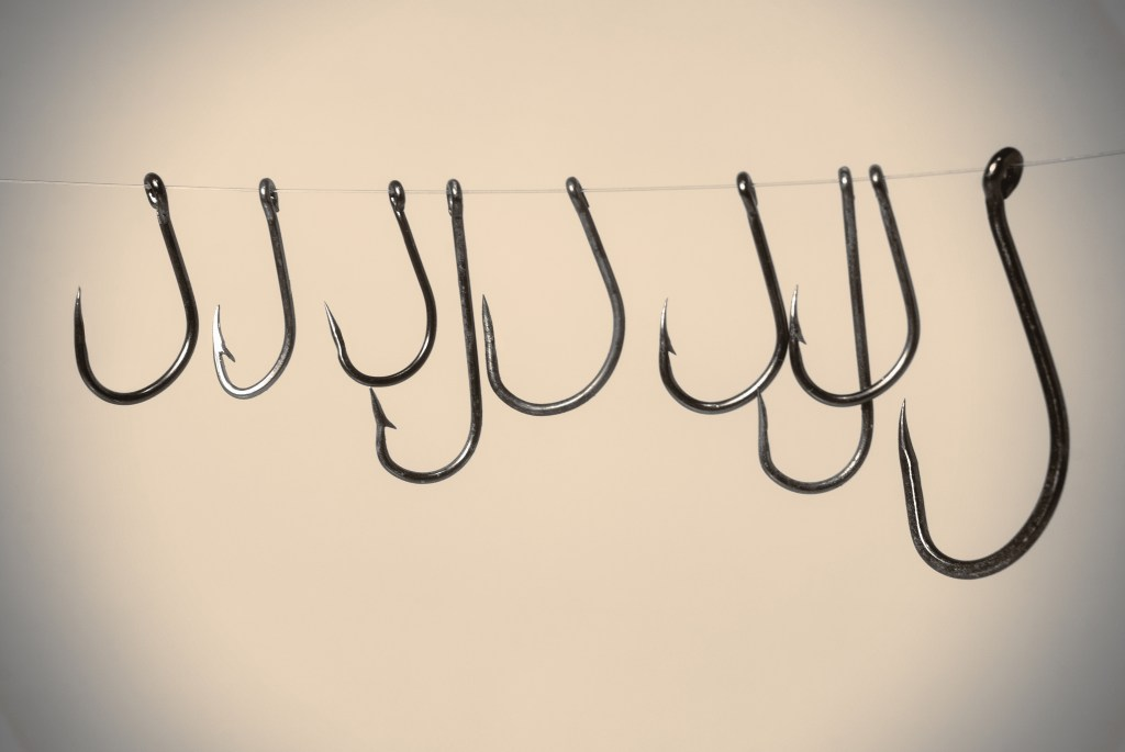 A set of fishing hooks on a string. Half of them are barbed, the other half are barbless