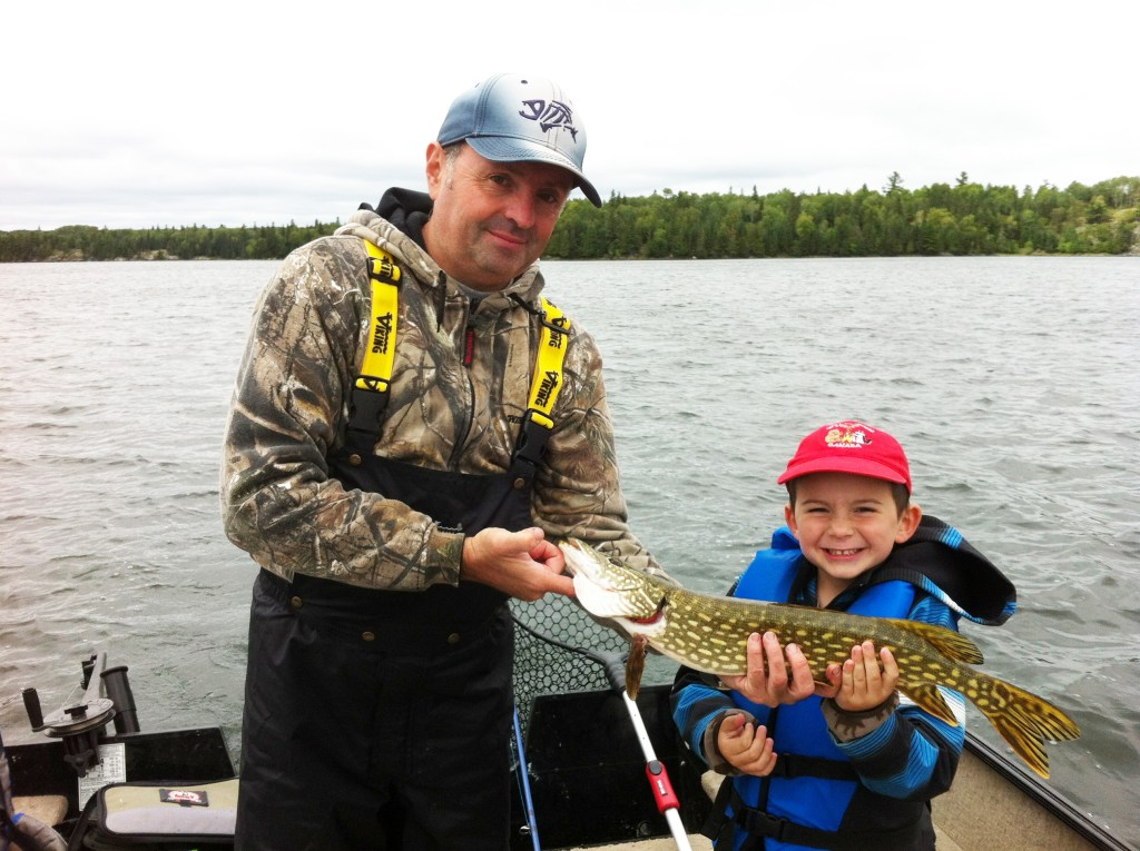 Fishing Lake Winnipeg: a boy angler holding a fish together with a fishing guide
