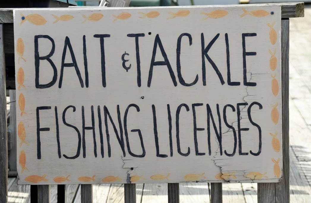 A shop outside a fishing shop advertising bait, tackle, and fishing licenses