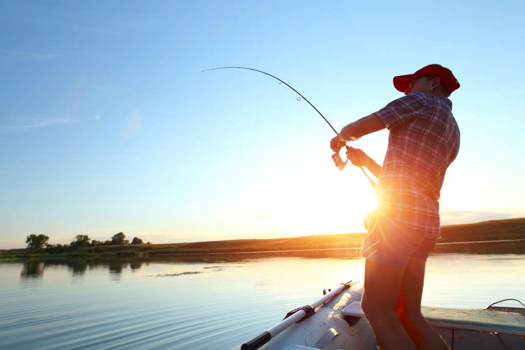 An angler fishing from a boat with blue skies and sunset in the background