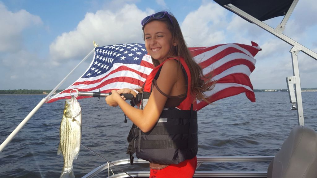 a smiling girl holding a Bass fish on a boat on Lake Conroe, with the American flag behind her