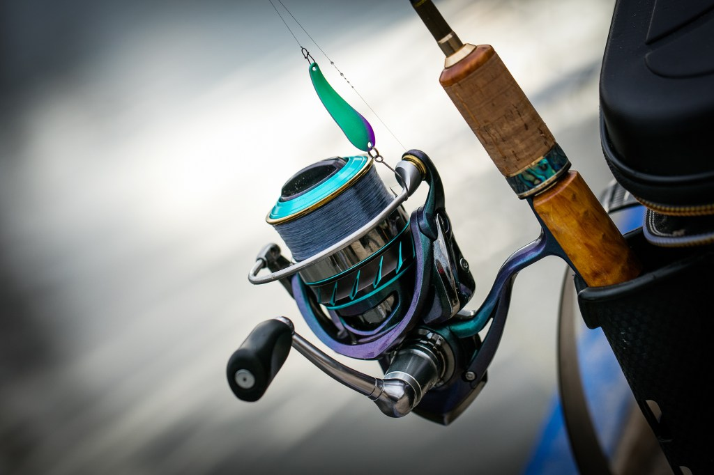 A spinning reel rigged with braid, with water in the background