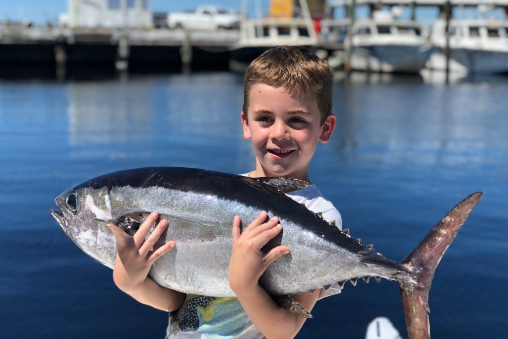 A smiling kid holding a Tuna he caught on a fishing trip