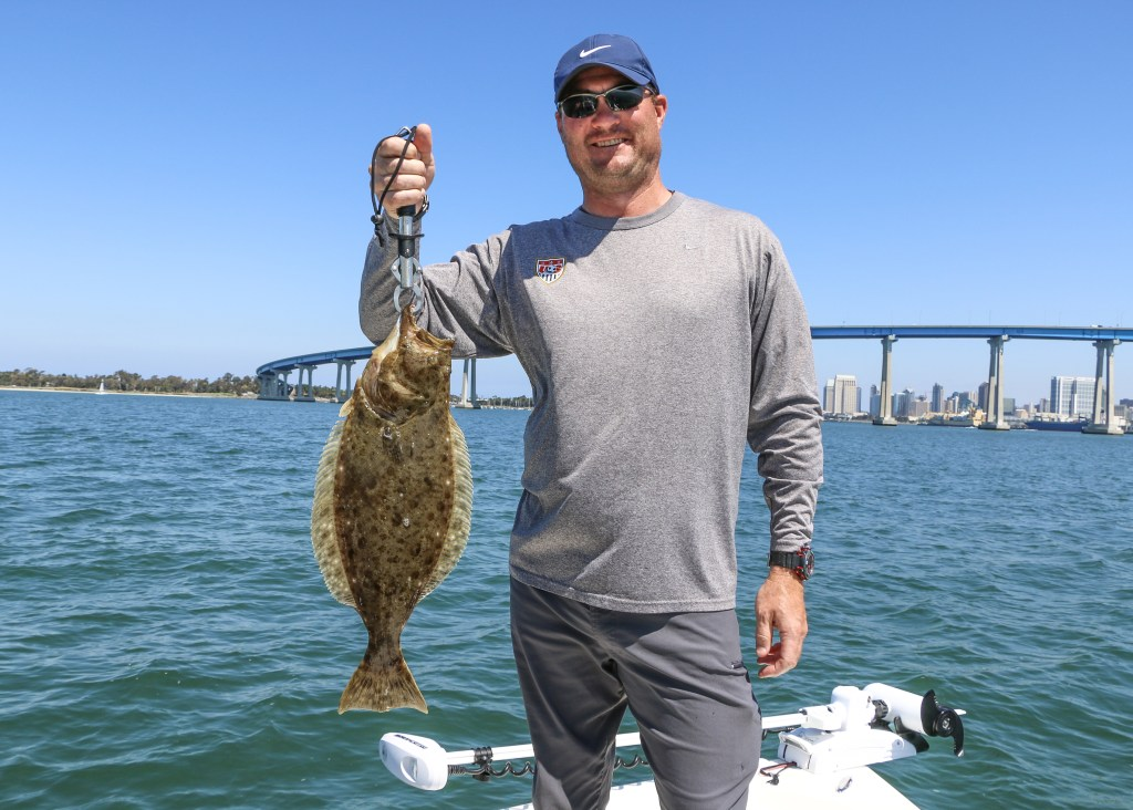 an angler holding a Halibut in San Diego Bay