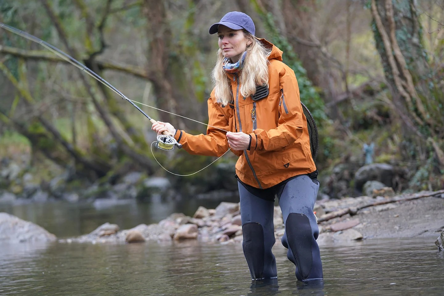A woman in an orange jacket fly fishing while wading in a stream