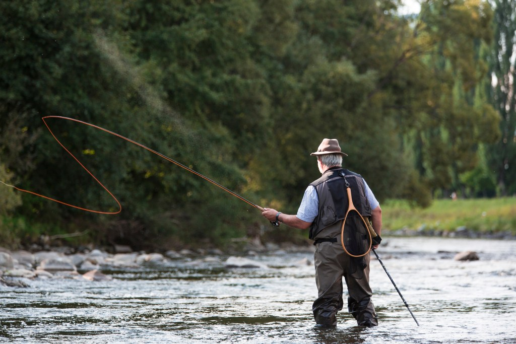 A fly fisherman making a cast while wading in a river