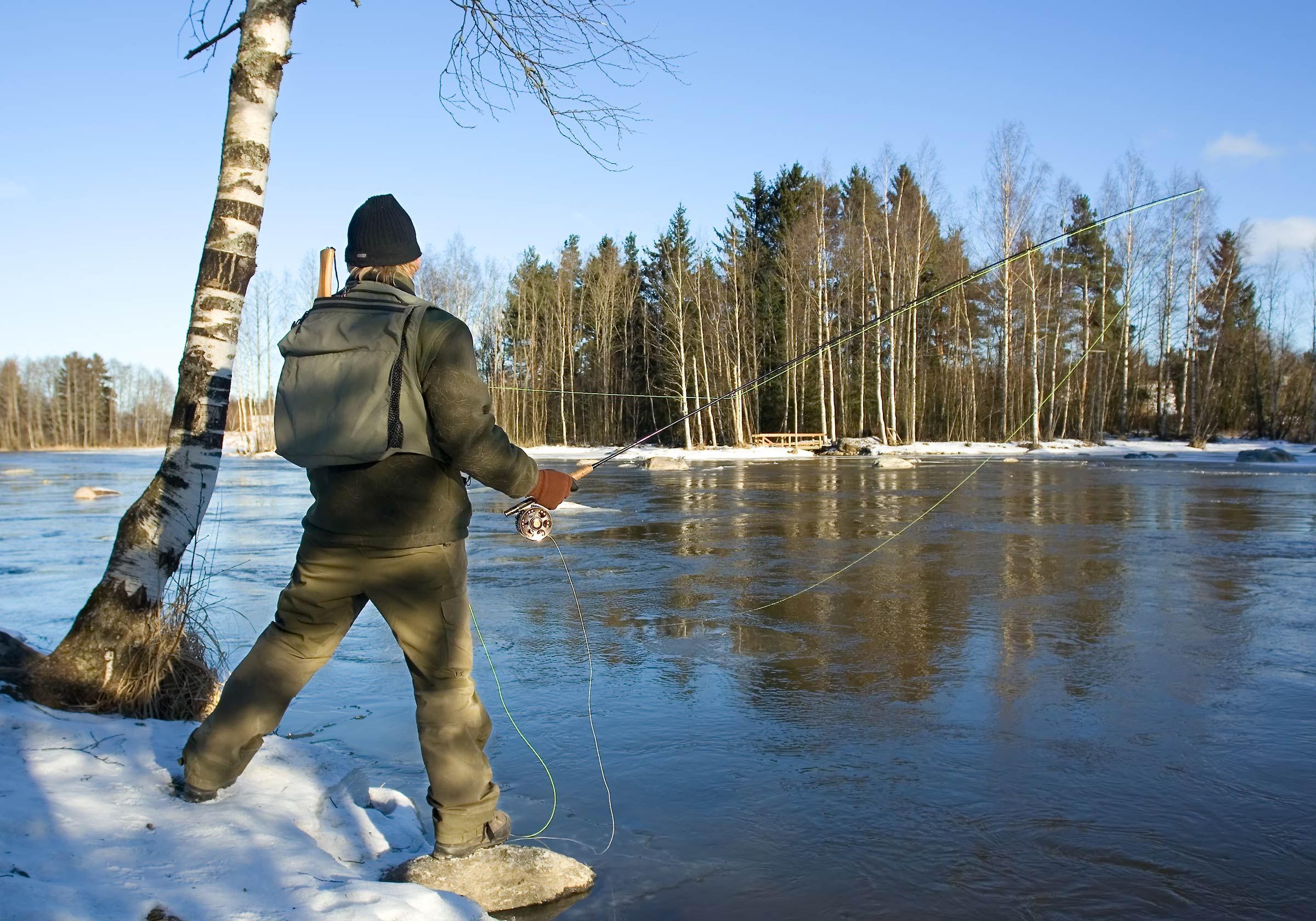 A fisherman fly fishing from a snow-covered lake shore