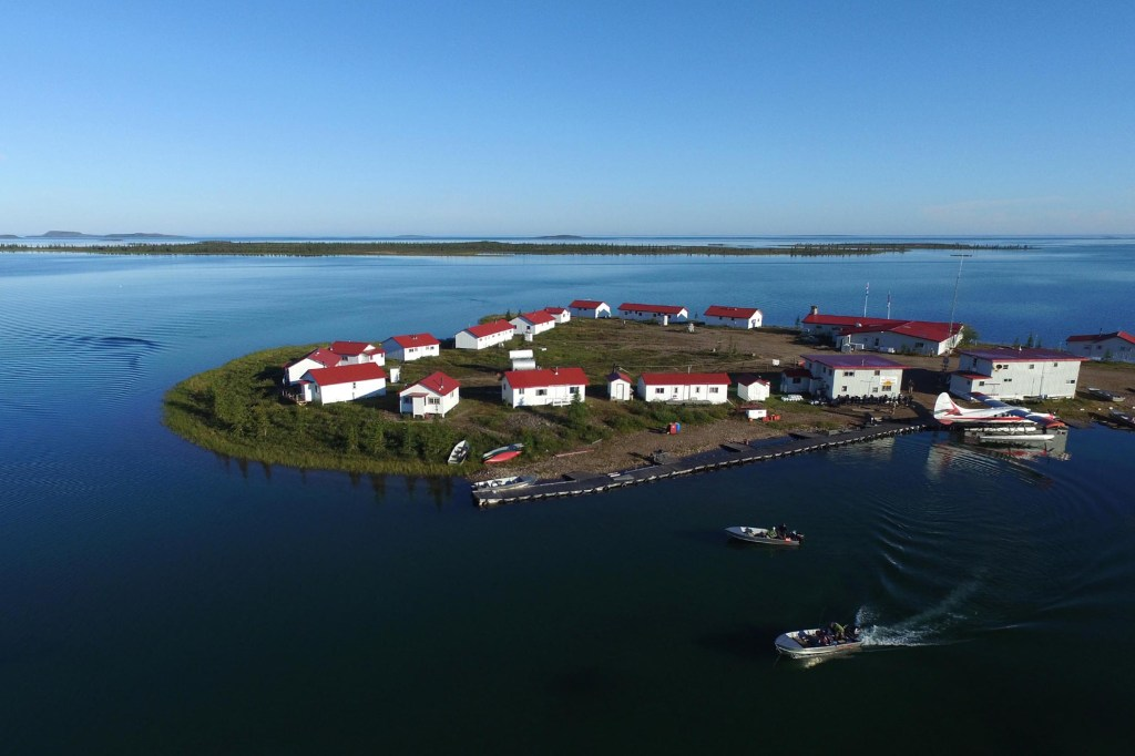 An isolated fly-in fishing lodge on an island in Northern Canada. Several small buildings dot the island, boats cruise in the local waters, and a small seaplane is moored by the shore