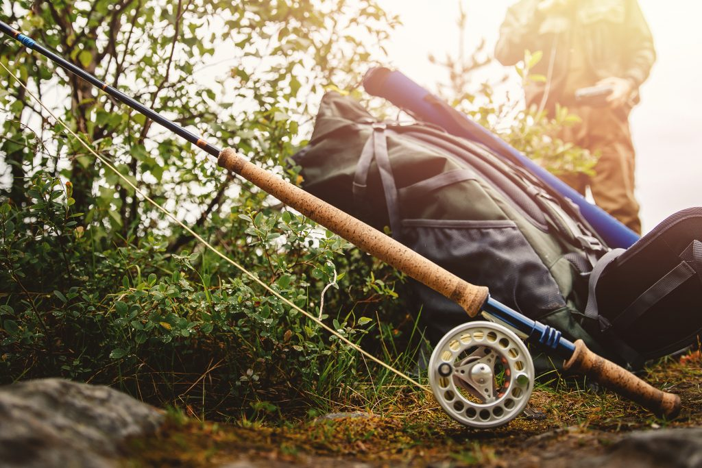 A fly fishing rod next to a backpack, with an angler standing behind