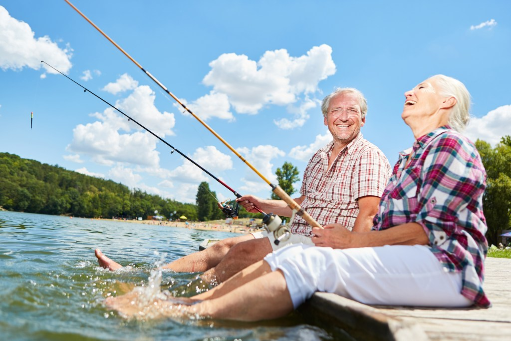 An elderly couple laughing and fishing with their feet in the water